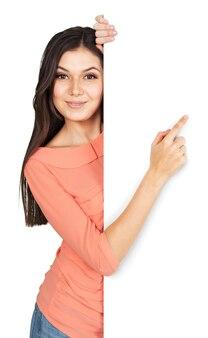 白い背景で隔離の空白の看板を示す幸せな笑顔の若い女性