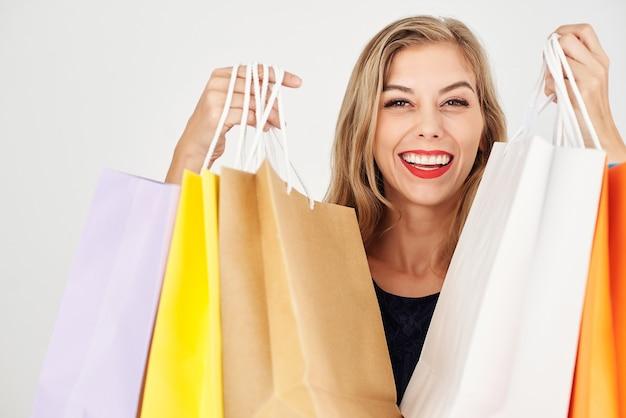 Счастливая улыбающаяся молодая женщина показывает сумки, полные покупок, изолированные на белом