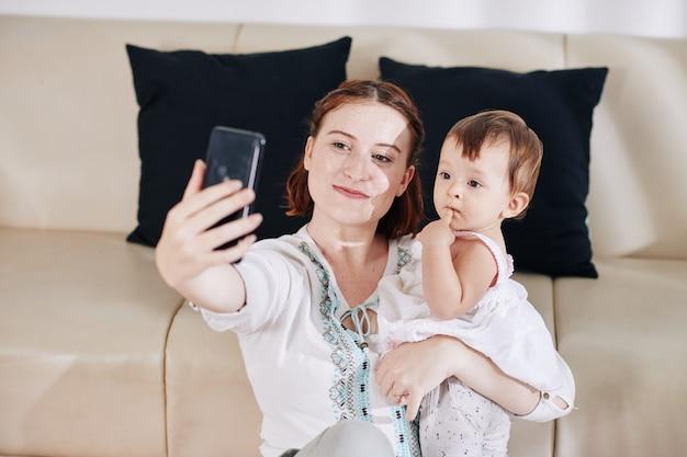 かわいい小さな赤ん坊の娘とselfieを取っている幸せな笑顔の若い女性