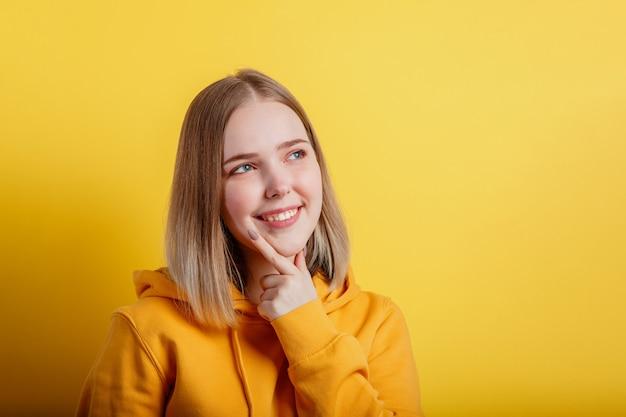 Счастливая улыбающаяся молодая женщина думает думала. портрет эмоциональной девочки-подростка, смотрящей на пустое пространство, глубоко думая об идее или положительном вопросе на цветном желтом фоне с копией пространства.
