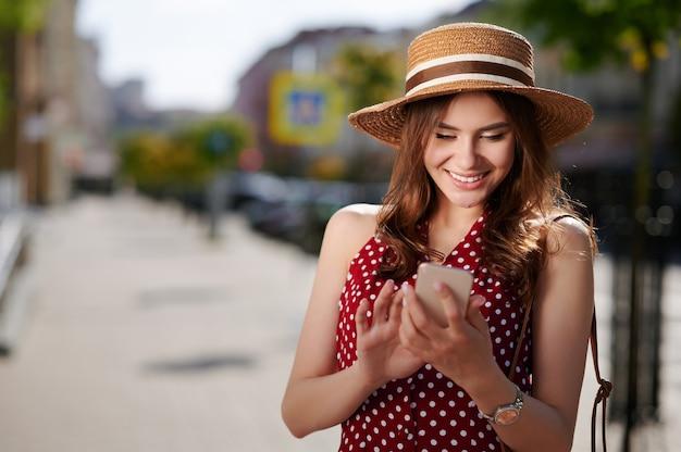야외에서 휴대 전화를 사용 하여 행복 하 게 웃는 젊은 여자 프리미엄 사진