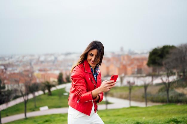 晴れた夏の日に公園を歩いている間、彼女の携帯電話を介してテキストメッセージまたはsmsを入力する現代のスマートフォンを使用して幸せな笑顔の若い女性。