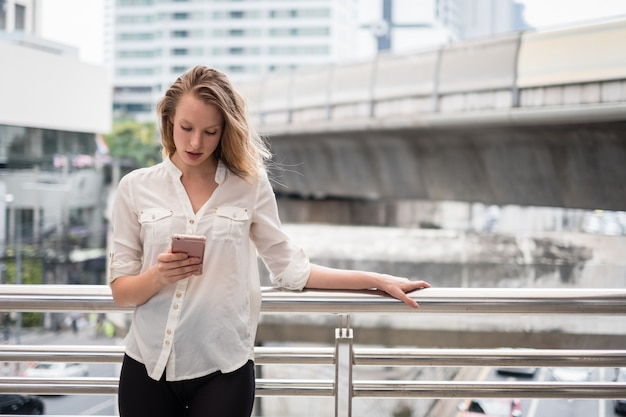 Happy smiling young woman using phone in the city with space for text