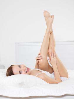 Счастливая улыбающаяся молодая женщина с красивыми ногами, лежа на кровати в спальне