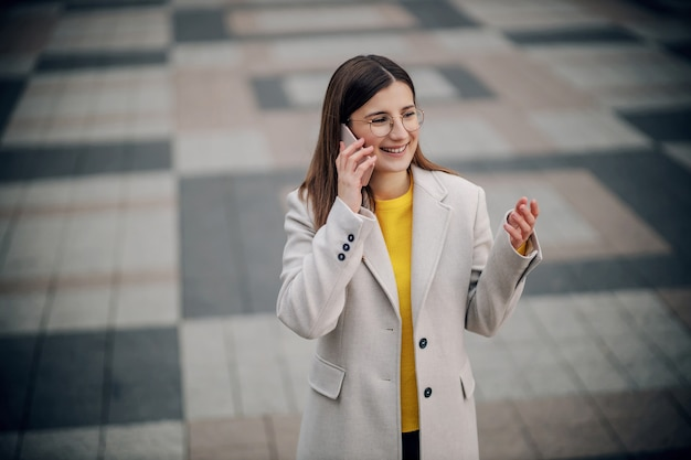 Happy smiling young woman in yellow sweater standing on city square and talking on the phone.