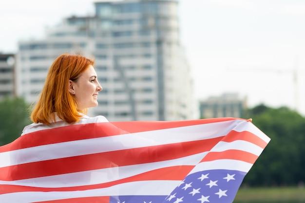 Счастливое усмехаясь молодое womanl с национальным флагом сша на ее плечах с высокими зданиями города празднуя день независимости соединенных штатов.