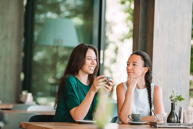 Счастливые усмехаясь молодые женщины с кофейными чашками на кафе.