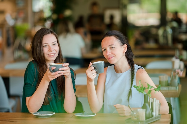 Happy smiling young women with coffee cups at cafe. communication and friendship concept