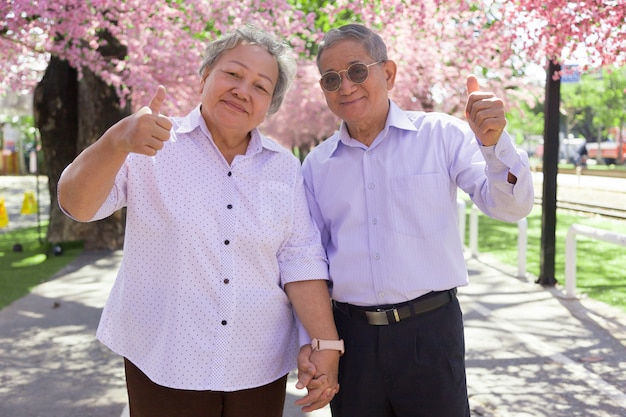 Happy smilling asian granfather and grand mother show thump up as confidence life on outdoor parking