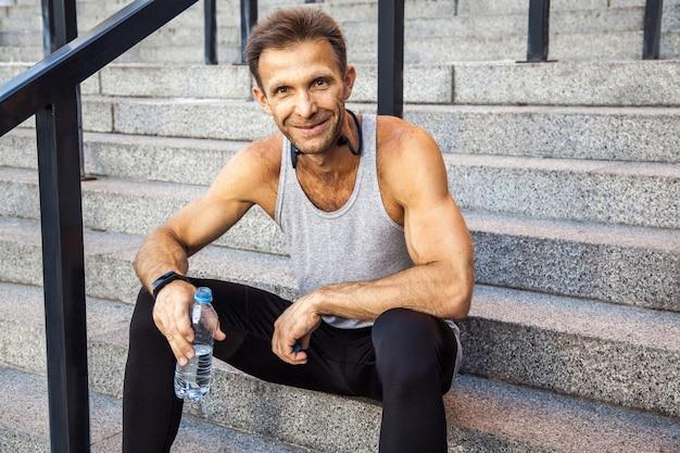 행복한 웃는 스포츠맨은 쉬고 물 한 병을 들고 계단에 앉아 카메라를 보고 웃고 있습니다. 피트 니스, 스포츠, 운동 및 사람들이 건강한 라이프 스타일 개념.