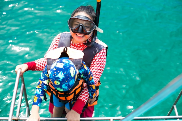 해피 스노클링 엄마와 아들은 태국 카리브해 휴가에서 바다 물 스노클링을 즐기고 있습니다.