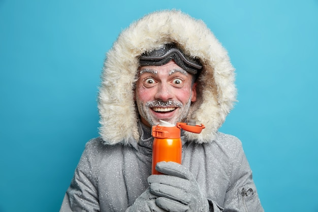 Happy snow man enjoys extreme sport during cold frosty day in mountains wears ski goggles and jacket warms with hot beverage has white frost on face. hiking mountaineering active rest concept