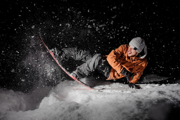 Happy snowboarder in orange jacket with stuck out tongue riding on a snowy hill at night