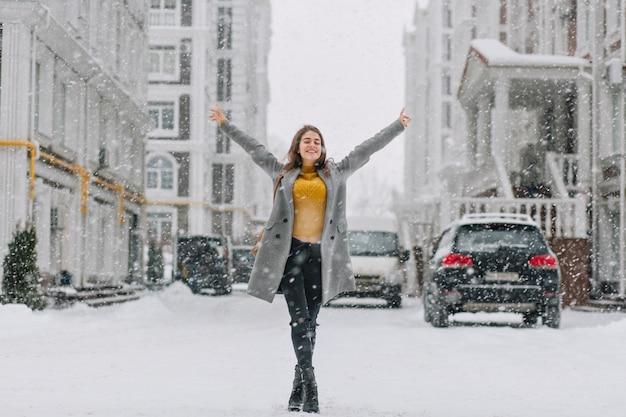 Orario invernale nevoso felice nella grande città della ragazza graziosa che gode della nevicata sulla strada. vere emozioni positive, tenendosi per mano in alto,