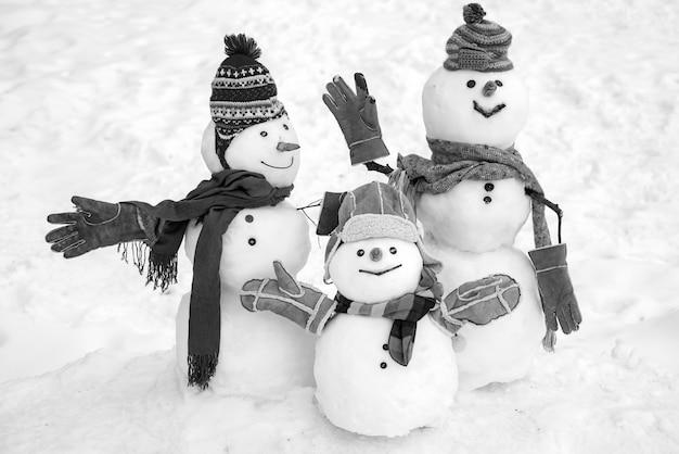Счастливая пара снеговиков и ребенок-снеговик с рождественским подарком, стоящий в зимнем рождественском пейзаже