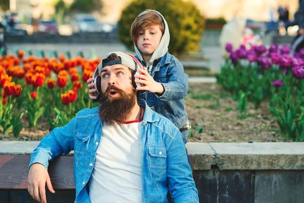 Счастливый сын и отец, с удовольствием на прогулке вместе. молодой отец с помощью беспроводных наушников слушать музыку. семья, концепция отношений.