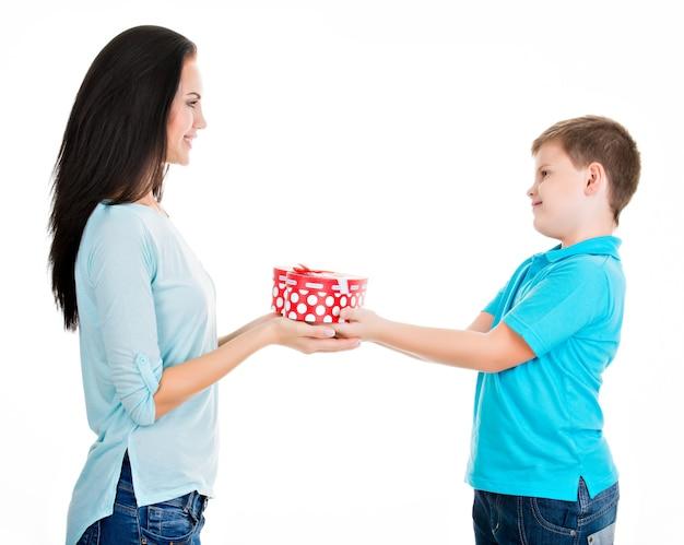 Счастливый сын делает подарок своей матери, изолированной на белом