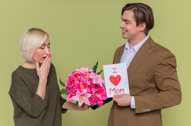 Счастливый сын дает поздравительную открытку и букет цветов своей матери, празднует международный женский день, стоя у зеленой стены