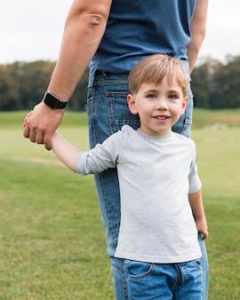 彼の父の手正面を保持している幸せな息子