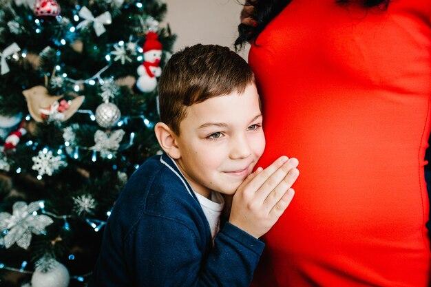 Счастливый сын обнимает маму, наслаждаясь отдыхом вместе с рождеством и счастливыми праздниками