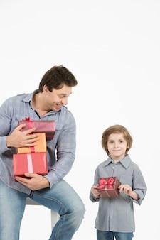 그의 아들을 껴안고 선물을주는 행복한 아들. 아버지의 날, 가족 휴가.