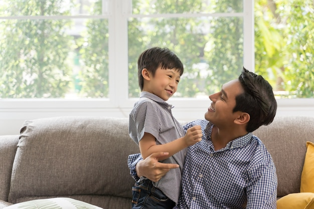 Happy son playing with father in living room.