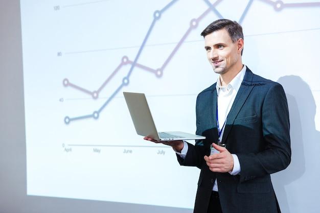 Счастливый спикер держит ноутбук и делает презентацию в конференц-зале