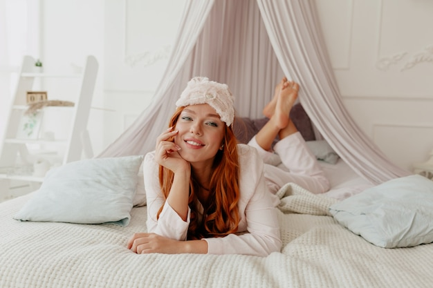 Happy spectacular woman with red wavy hair wearing sleeping mask and pajamas lying on the bed with charming smile