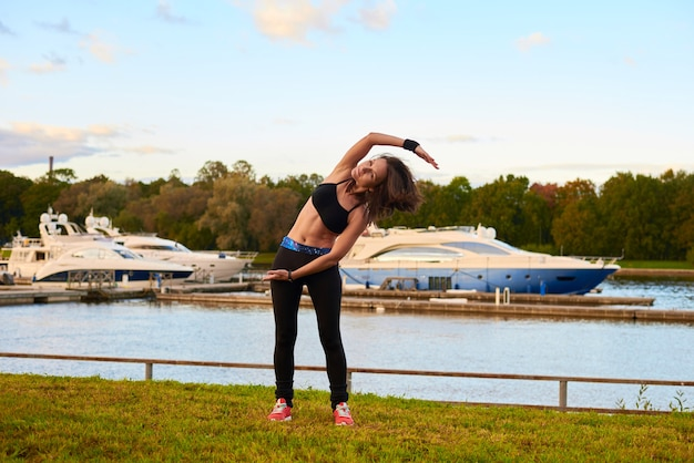 Donna castana di sport felice in canotta nera e collant che fanno allungamento laterale in piedi. concetto di formazione serale sulla spiaggia della vita salutare.