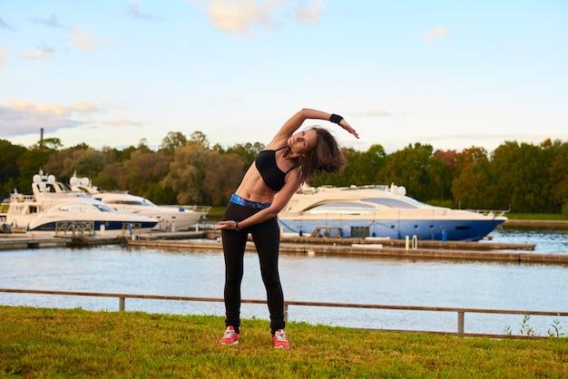 黒のタンクトップとタイツで立っている横方向のストレッチを作る幸せなスポーツブルネットの女性。健康生活のイブニングビーチトレーニングのコンセプト。