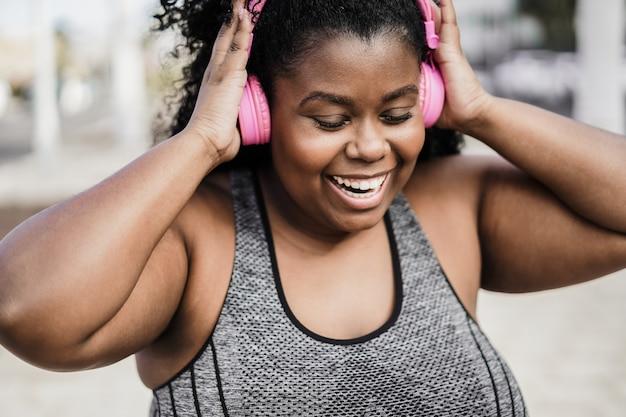 Счастливая спортивная фигуристая черная женщина слушает музыку в наушниках - фокус на лице