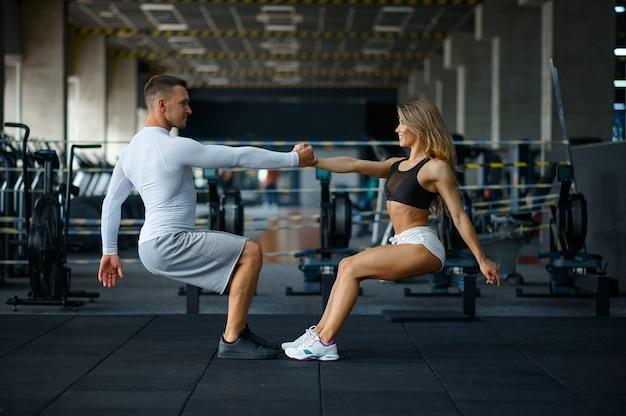 팔 굽혀 펴기를 하는 행복한 낚시를 좋아하는 커플, 체육관에서 훈련