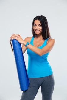ヨガマットを保持している幸せなスポーツの女性
