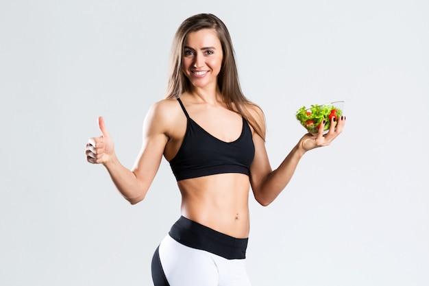 分離したサラダとハッピースポーツ女性。