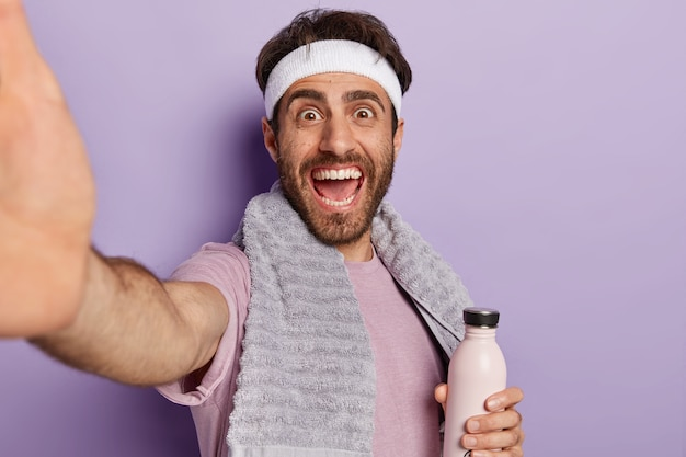 Happy sportsman extends hand and takes selfie during workout, holds water bottle, stays hydrated and healthy,  wears towel on neck isolated on purple wall