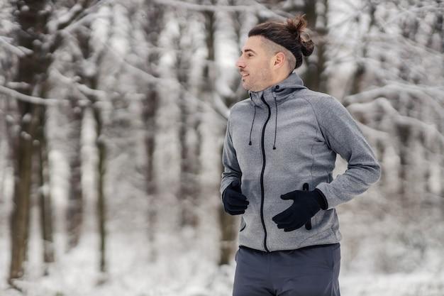 눈 덮인 겨울 날 자연 속에서 달리는 행복한 스포츠맨. 건강한 생활 방식, 유산소 운동, 겨울 스포츠