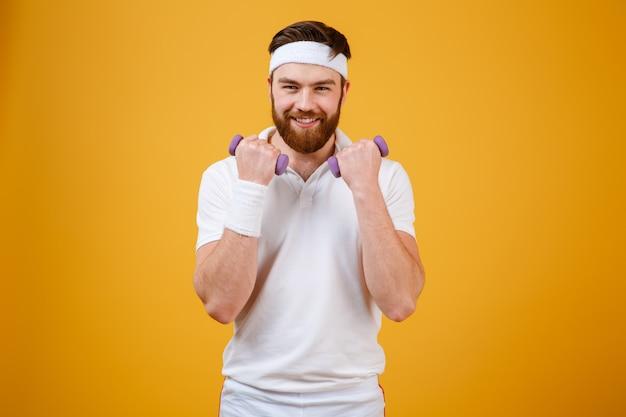 Счастливый спортсмен с легкими гантелями