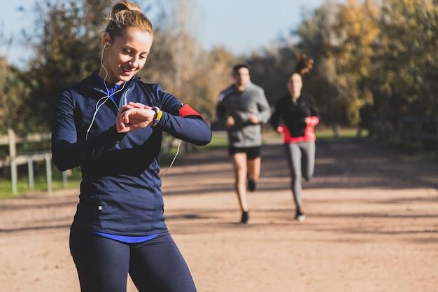 Happy sportswoman controlling her beats