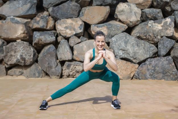 Happy sportswoman doing side lunge