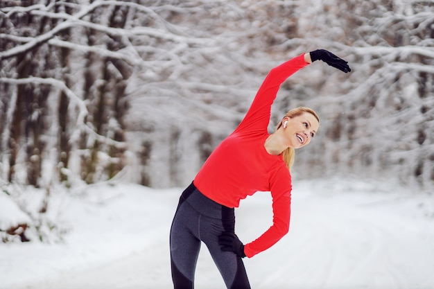 Happy sportswoman doing stretching exercises while standing on snowy path in woods at winter. winter fitness, warm up exercises