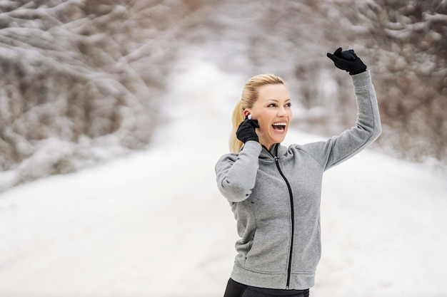 Happy sportswoman enjoying music and taking a break from exercising while standing in nature at snowy winter day