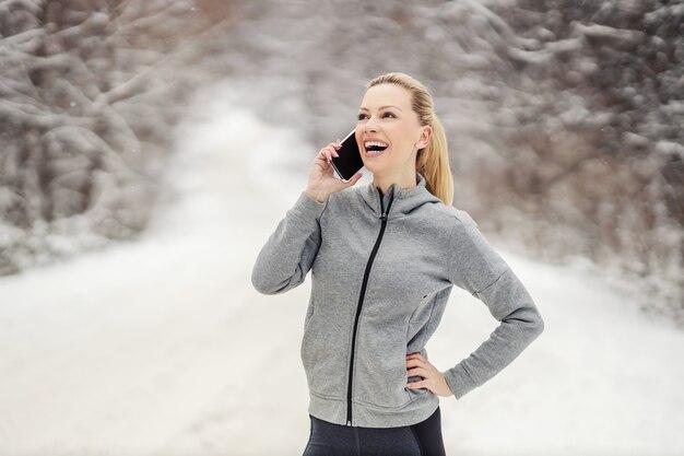 Счастливая спортсменка в форме, стоя на природе в снежный зимний день и имея телефонный звонок. телекоммуникации, зимний фитнес, технологии
