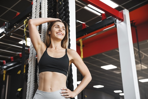 Happy sportswoman leans near a crossfit battle rope stand, smiling delighted, exercise in health club