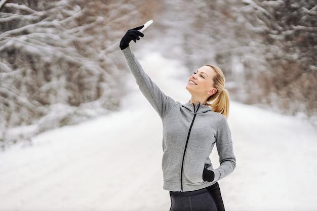 雪の降る冬の日に自然の中で立って、ソーシャルメディアのために自分撮りをしている幸せなスポーツウーマン。ソーシャルメディア、電気通信、冬のフィットネス