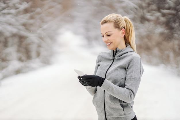 Счастливая спортсменка, стоящая на природе в снежный зимний день и использующая свой телефон для текстовых сообщений. технологии, телекоммуникации, зимний фитнес
