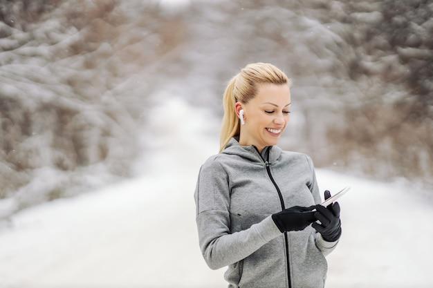 눈 덮인 겨울 날 자연 속에 서서 휴대전화로 음악을 검색하는 행복한 스포츠우먼. 기술, 통신, 겨울 피트니스
