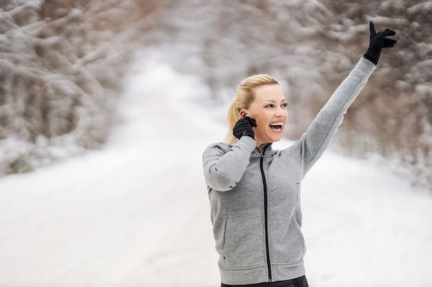 雪の降る冬の日に自然の中で立って、イヤホンを持って音楽を楽しんでいる幸せなスポーツウーマン。テクノロジー、楽しさ、冬のフィットネス