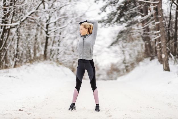 Счастливая спортсменка, стоящая на заснеженной тропе на природе и делающая упражнения на разминку и растяжку перед бегом. здоровый образ жизни, зимний фитнес