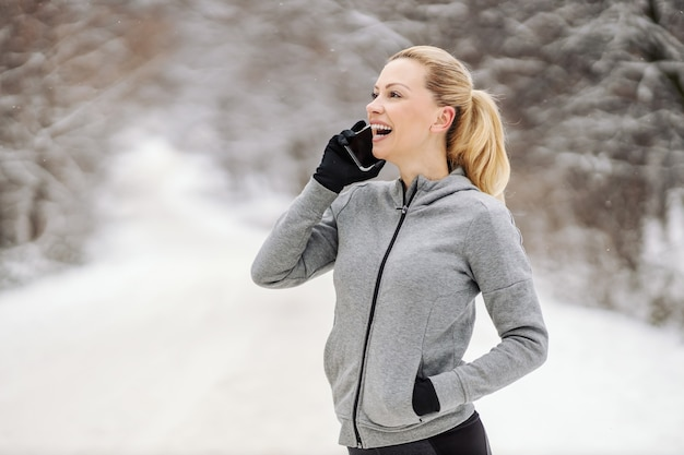 Happy sportswoman taking a break from exercises and having phone call while standing in nature at snowy winter day.