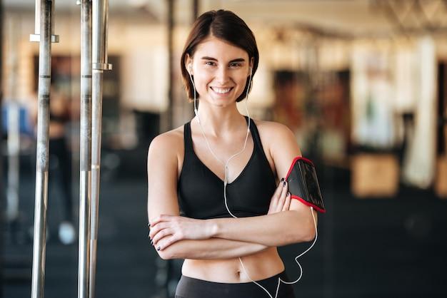 Счастливая спортсменка с повязкой слушает музыку в тренажерном зале